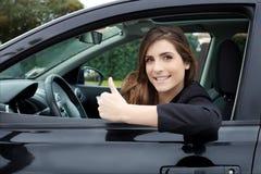 Glückliche junge Frau im Neuwagen, der oben lächelnden Daumen der Kamera schaut Stockfotografie