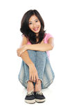 Glückliche junge Frau im Sitzen der beiläufigen Abnutzung Stockfotografie