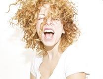 Glückliche junge Frau mit dem unordentlichen lockigen Haar Lizenzfreies Stockfoto