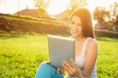 Glückliche junge Frau mit Tablette im Park am sonnigen Sommertag Stockfotos