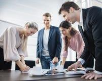 Glückliche junge Geschäftsleute, die am Konferenztische gedanklich lösen Lizenzfreies Stockfoto