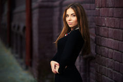 Glückliche junge Modefrau im schwarzen Kleid an der Backsteinmauer Stockfotos