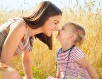 Glückliche junge Mutter mit kleiner Tochter auf Feld am Sommertag Stockfotografie
