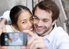 Glückliche junge Paare, die ein selfie und ein Lächeln nehmen Stockbild