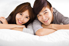 Glückliche junge Paare, die in einem Bett liegen Lizenzfreies Stockbild