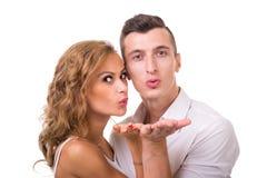 Glückliche junge Paare, die einen Schlagkuß zu schicken Stockbilder