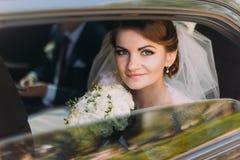 Glückliche junge Paare im luxuriösen Auto nach ihrer Hochzeit Konzentrieren Sie sich auf die schöne Braut und an der Kamera läche Stockbild