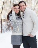 Glückliche junge Paare mit dem Mistelzweig, der Spaß im Winter hat Lizenzfreie Stockfotografie