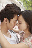 Glückliche junge Paare mit den Armen um einander, das Stirnberühren und die Augen schlossen Stockbilder