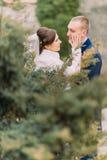 Glückliche Jungvermähltenpaare, Braut und Bräutigam, am Hochzeitsweg auf dem schönen grünen Park Stockfotografie