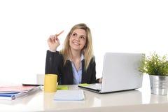 Glückliche kaukasische blonde Geschäftsfrau, die an Laptop-Computer am modernen Schreibtisch arbeitet Lizenzfreies Stockfoto
