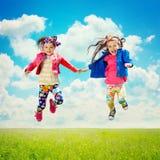 Glückliche Kinder, die auf das Frühlingsfeld springen Stockfoto