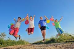 Glückliche Kinder, die auf Feld mit Ballonen springen Lizenzfreie Stockbilder