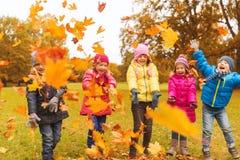 Glückliche Kinder, die mit Herbstlaub im Park spielen Stockbilder