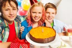 Glückliche Kinder mit Geburtstagskuchen und -kerze Stockbild