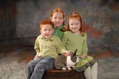 Glückliche Kinder mit Kaninchen Stockbild