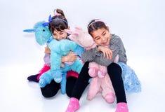 Glückliche kleine Mädchen, die Einhornspielwaren lokalisiert auf Weiß halten Stockfoto