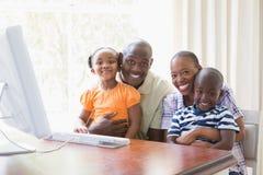 Glückliche lächelnde Familie des Porträts unter Verwendung des Computers Stockbild