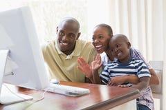 Glückliche lächelnde Familie, die mit Computer chattting ist Stockfoto
