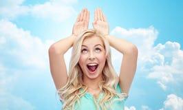 Glückliche lächelnde junge Frau, die Häschenohren herstellt Lizenzfreies Stockbild