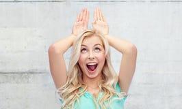Glückliche lächelnde junge Frau, die Häschenohren herstellt Stockfoto