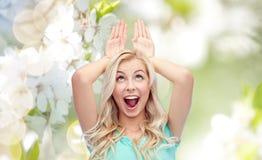 Glückliche lächelnde junge Frau, die Häschenohren herstellt Lizenzfreie Stockfotos