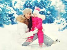 Glückliche lächelnde Mutter und Kind, die auf Schnee im Winter sitzt Stockfotografie