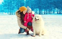 Glückliche lächelnde Mutter und Kind mit weißem Samoyedhund im Winter Stockfotos