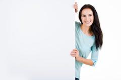 Glückliche lächelnde schöne junge Frau, die leeres Schild zeigt Stockfotos