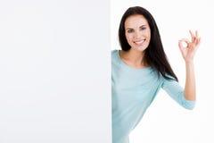 Glückliche lächelnde schöne junge Frau, die leeres Schild zeigt Stockfotografie