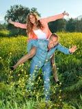 Glückliche lebhafte junge Paare, die piggyback reiten Stockbild