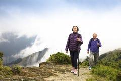Glückliche ältere Paare, die auf dem Berg wandern Stockfoto