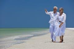 Glückliche ältere Paare, die auf Meer auf Strand zeigen Stockfotos