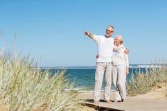 Glückliche ältere Paare, die auf Sommerstrand umarmen Lizenzfreie Stockfotos