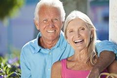 Glückliche ältere Paare, die draußen im Sonnenschein lächeln Stockfoto