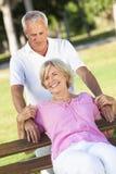 Glückliche ältere Paare, die draußen im Sonnenschein lächeln Lizenzfreies Stockbild