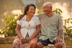 Glückliche ältere Paare, die draußen sitzen Stockfoto