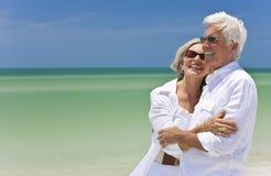 Glückliche ältere Paare, die zum Meer auf Strand schauen Lizenzfreies Stockfoto