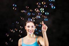 Glückliche Mädchen- und Seifenluftblasen Stockfotos