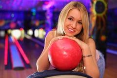 Glückliche Mädchenunterseiten auf Kugel im Bowlingspiel schlagen mit einer Keule Lizenzfreie Stockfotos