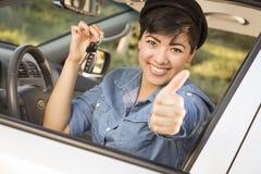 Glückliche Mischrasse-Frau im Auto, das Schlüssel hält Stockfoto