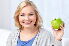 Glückliche mittlere Greisin mit grünem Apfel zu Hause Stockfoto