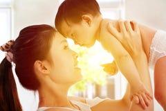 Glückliche Mutter, die entzückendes Kinderbaby mit Sonnenaufgang backgroun hält Stockfotografie
