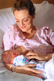 Glückliche Mutter, die neugeborenes Baby pflegt Stockbild