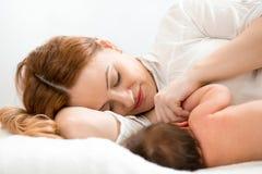 Glückliche Mutter, die neugeborenes Baby stillt Lizenzfreie Stockfotos