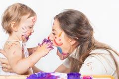 Glückliche Mutter und Baby, die mit gemaltem Gesicht durch Farbe spielt Lizenzfreie Stockfotos
