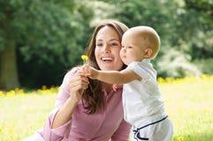 Glückliche Mutter und Kind, die Blume im Park hält Lizenzfreies Stockfoto