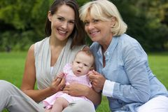 Glückliche Mutter und Kind, die draußen mit Großmutter sitzt Lizenzfreie Stockfotografie