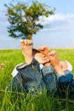 Glückliche Paare, die auf einer Wiese liegen Lizenzfreie Stockbilder