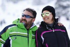 Glückliche Paare, die im Schnee genießen Stockfoto